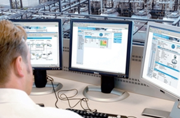 Man viewing three computers while overlooking a production facility