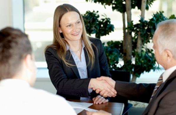 Woman and man shaking hands at a meeting