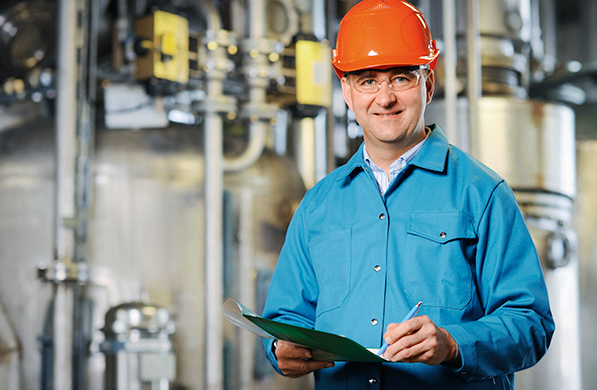 Man with clipboard and hard hat in a plan environment